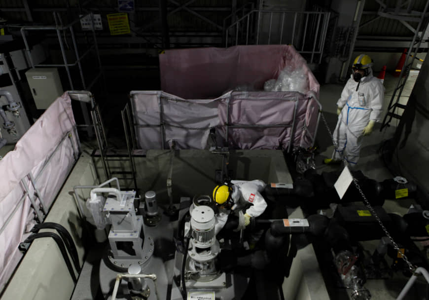 Employees of TEPCO wearing protective suits and masks are seen inside a radiation filtering  ALPS at tsunami-crippled Fukushima Daiichi nuclear power plant in Okuma town, Japan