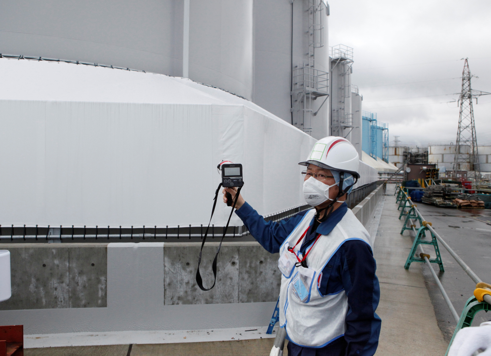 An employee of Tokyo Electric Power Co's uses a geiger counter next to storage tanks for radioactive water at tsunami-crippled Fukushima Daiichi nuclear power plant in Okuma town, Fukushima prefecture